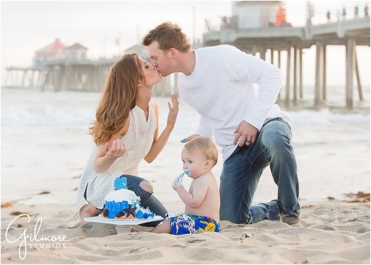 Foster's 1st birthday - Cake Smash Portrait Session - Huntington Beach Photographer, HB, Huntington Beach, Cali, CA, California, beach, ocean, sunset, cake smash, portrait session, first birthday, one year old, adorable, precious, darling, baby swim trunks, baby boy, checkered shirt, pier, HB pier, family, french's bakery, cake, ocean themed cake, blue whale cake, mom and dad kiss, kiss, kissing, baby eating cake, frosting everywhere, messy baby, frosting on face, finger food…