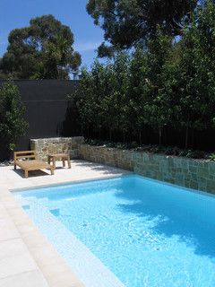 nice small family pool completed with white tiles, Anston Bondi paving and Eco Clancy wall panelling. Design and photography by Dean Jones