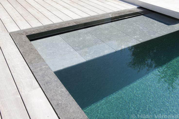 Dit betonnen zwembad werd aangelegd in een eerder kleine tuin. Het terras in paddoek en de bekleding in mozaïek geven het een luxueuze uitstraling.Klik hier