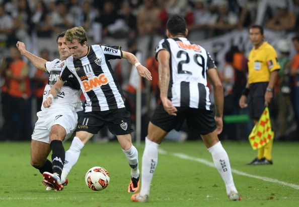 Atletico Mineiro's Bernard (2-L) vies for the ball with Paraguayan Olimpia's forward Juan Salgueiro (L) during their Libertadores Cup second leg football match at the Mineirao stadium in Belo Horizonte, Brazil on July 24, 2013