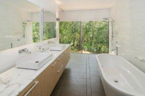 Ein trendiges Badezimmer mit eine freistehende Badewanne, Kopfbrause, Waschbecken und Flachbildschirm-Schränke. / Foto von Rodrigues Bodycoat Architekten