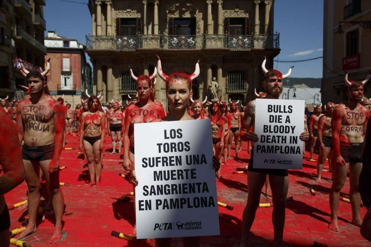 Protesters hold placards reading 'Bulls die a bloody dead in Pamplona' as other animal rights activists wearing body painting reading 'stop bullfights' protest ahead of San Fermin Running of the bulls on July 5, 2017 in Pamplona, Spain. Animal rights organizations Ethical Treatment of Animals (PETA) and Anima Naturalis organized today a performance to claim a San Fermin festivities with no blood and the abolition of bullfightings. Protesters wearing fake horns broke a 'banderilla'…