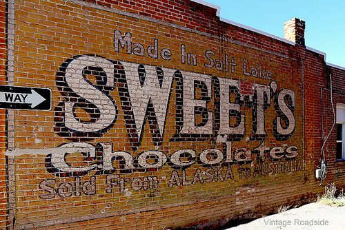 Vintage painted wall sign advertising Sweet's Chocolates in Panguitch, Utah.