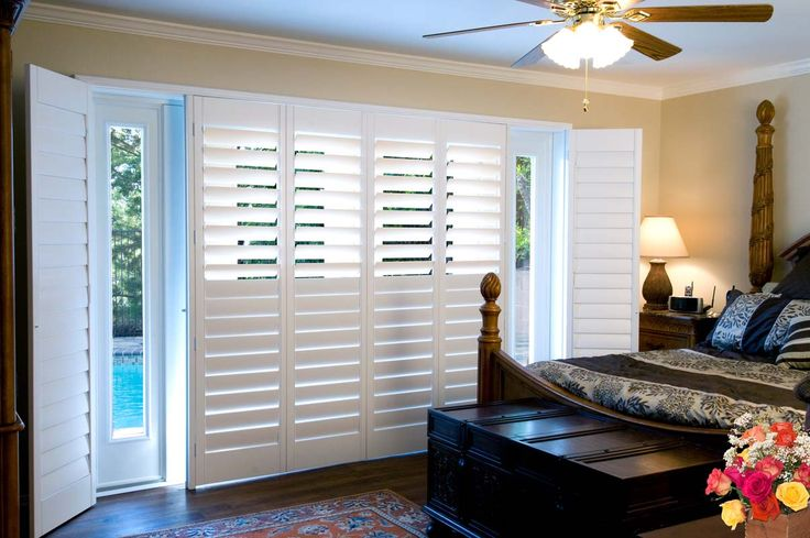 Thermalite custom shutters with hidden tilt rod and double-hung in bedroom overlooking pool