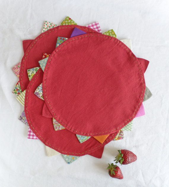 Red round placemat with colorful triangles. by TableStories