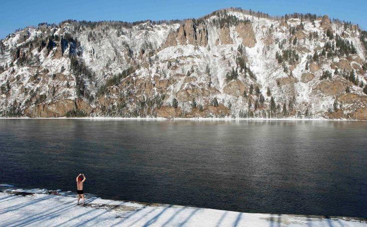 Vladimir Korabelnikov warms up on the bank of the Yenisei River in Divnogorsk
