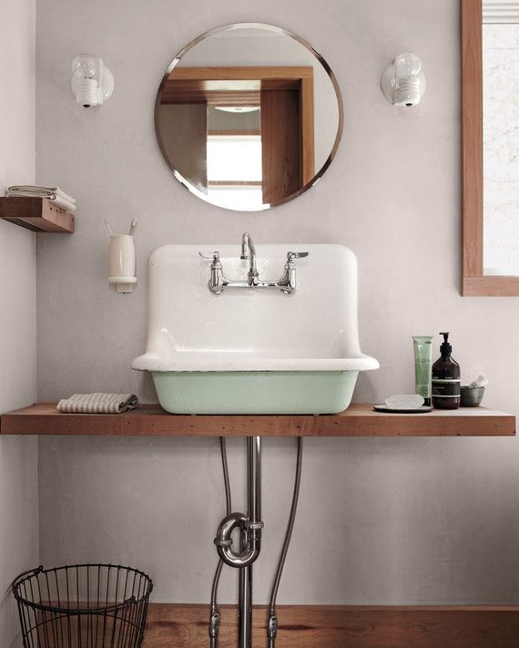 """The sink, painted the green of native lichen, is from a local salvage yard; they placed it on a shelf and left the plumbing exposed """"for both aesthetic and economic reasons."""""""