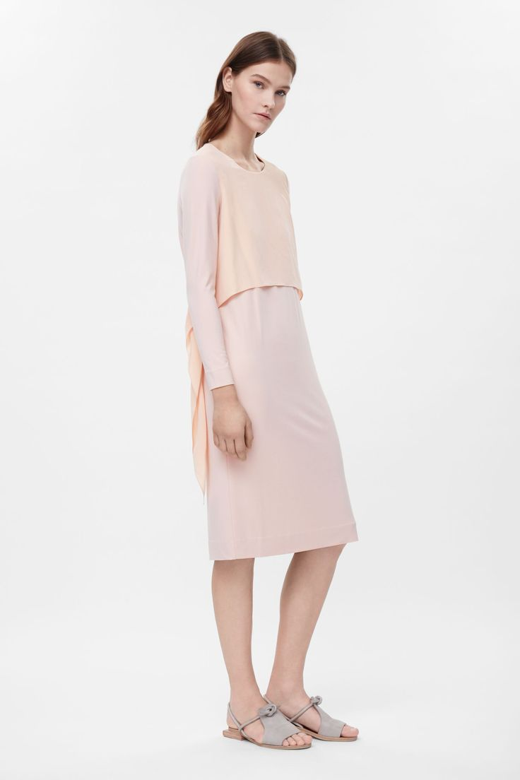 This dress is made from a comfortable stretchy material with a silk detail that can be tied in the back or left hanging to the sides. A close fit, it has a neat round neckline, long sleeves and clean edges.