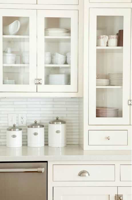 source: Ashlee Raubach Photography Lovely kitchen design with white linear  glass tiles backspalsh, white shaker glass-front kitchen cabinets, ...