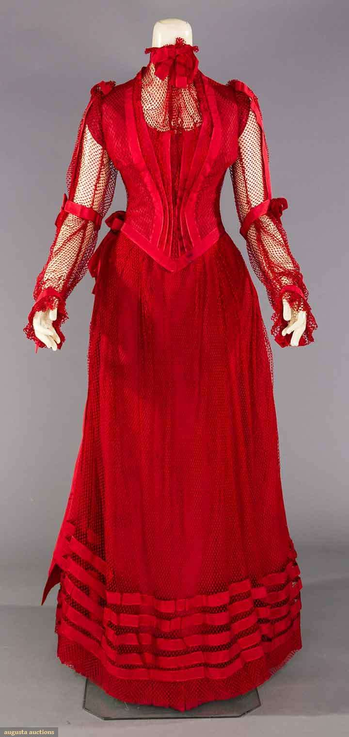 "BLOOD RED PARTY GOWN, PITTSBURG, PA. c. 1890 | Lot: 283 May 9, 2017 - CATALOG SALE Sturbridge, Massachusetts | 2-piece, red silk faille covered w/ red cotton mesh & red silk ribbon trims, boned & weighted bodice w/ see though yoke & sleeves, small bustle on skirt, label ""Misses Pence & Erwin 952 Penn Avenue Pittsburgh, PA"", small hidden pocket under CF closure, B 32"", W 23.5"", Skirt L 43""-46"", (some black stains to ribbons at CF bodice closure, holes in net, dirty hem proctector) fair."
