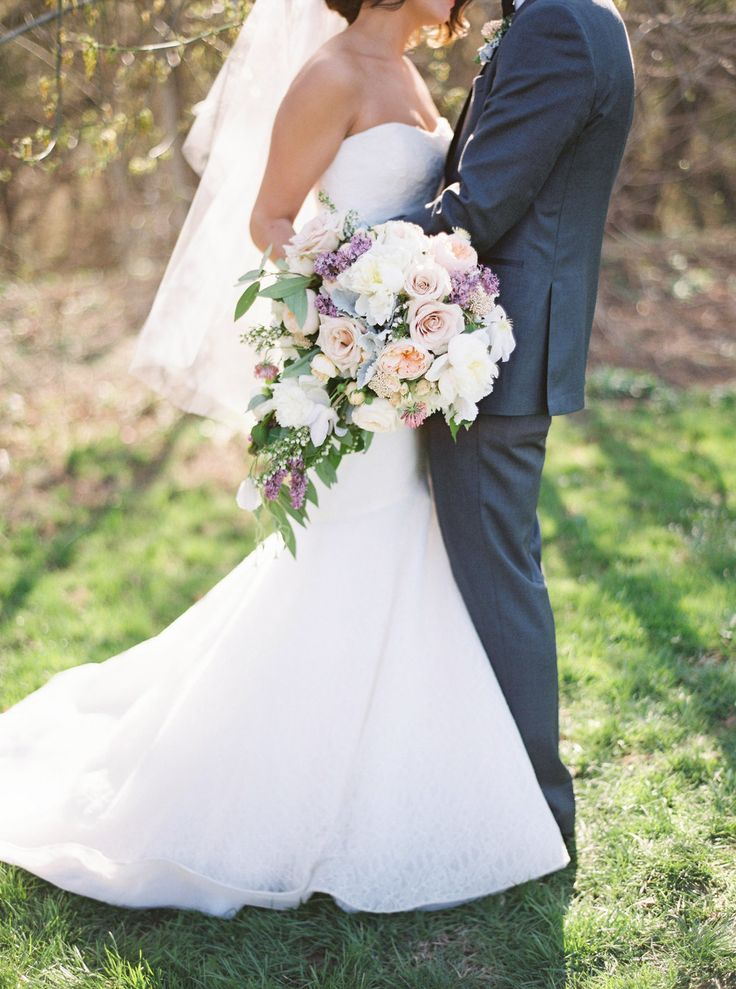 Lush blush, lavender, and peach cascading spring bouquet of garden roses, rice flower, peonies, lilac and greenery | Riverside on the Potomac wedding with Wild Green Yonder Flowers | Amelia Johnson Photography | Roberts and Co. Events