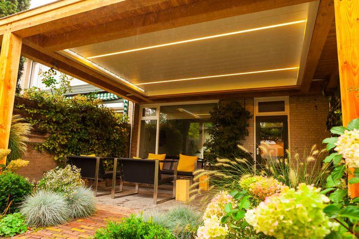 Lamellen dak veranda met houten ombouw. Door middel van de eenvoudige bediening, kunt u de lamellen geruisloos kantelen en realiseert u ideale lichtinval en ventilatie in een handomdraai. Ook bij het openen van de lamellen na een regenbui zijn uw meubelen op het terras beschermd. Dit gepatenteerde lamelledak is zo ontwikkeld dat het water wordt afgevoerd via de zijkant. http://denkit.nl/Producten/Renson-Camargue.html