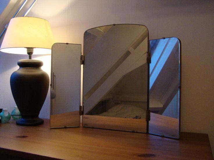 #31: Oude spiegel drieluik op hout. De spiegel is inklapbaar. Leuk boven een toilettafel of in de badkamer. Afmetingen uitgeklapt: b.64 x h.52 cm Afmetingen ingeklapt: b. 32,5 x h. 52 cm € 65,-