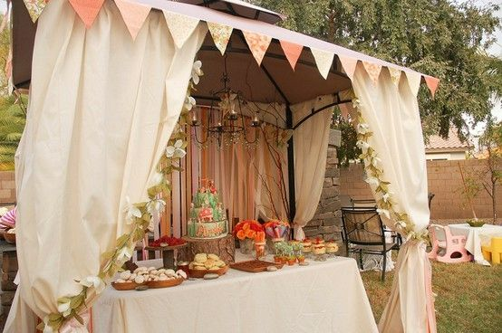Use sheets with floral garland to dress up simple tent. Use stump for cake stand. Use bunting for banner across front of tent.