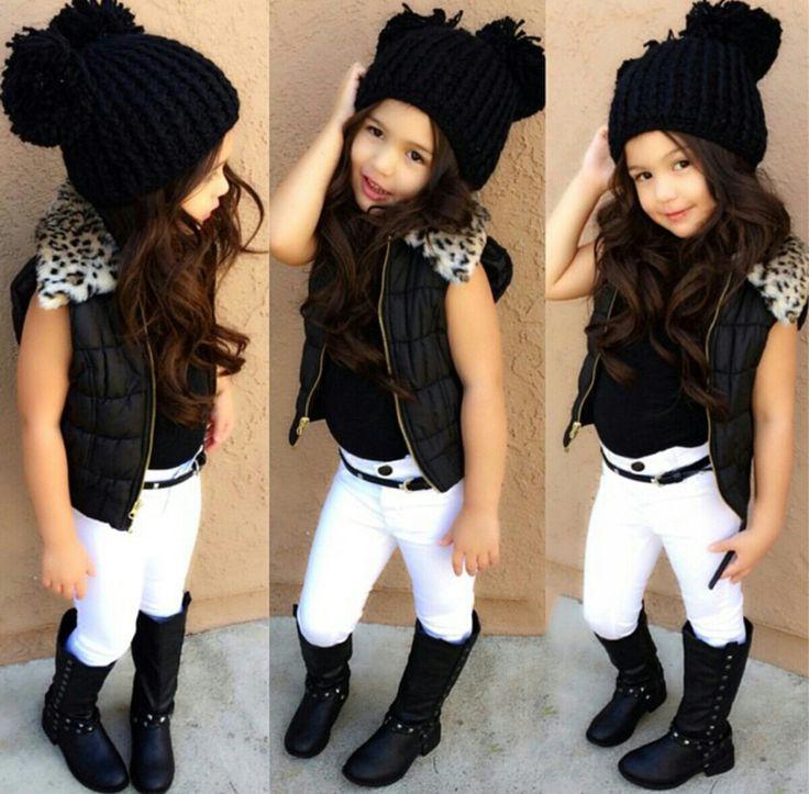 Niña usando un pantalón blanco chaleco botas , y gorro color negro