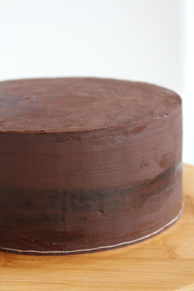 Rohling, glatt mit Ganache eingestrichen, darunter Schokoladen-Sponge-Cake
