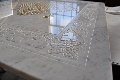 Using the Chippendale Molding stencil in vinyl form, he etches the design onto a Statuary Marble backsplash.  The Carrara Marble below has been acid etched with a custom Modello® vinyl stencil with the center area gilded.