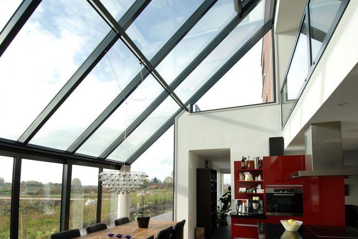 Prachtige luchten als uitzicht en zonlicht straalt binnen bij deze ruime en elegante serre van Reynaers aluminium.