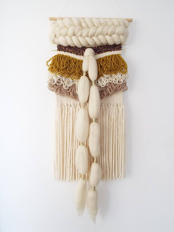 Unique woven wall hanging in ivory, beige and mustard with golden highlights, incorporating wool, cotton, ribbon, roving and Liberty of London fabric. This piece measures approximately 10 inches in width x 29 inches in length and hung onto a wooden dowel. A Bohemian inspired weaving ideal for any modern home. Custom orders welcome just email. Thanks for stopping by! © Anita Meades 2017