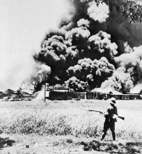 A Japanese soldier looks on as the oil refinery at Palembang in the Dutch East Indies burns.  Japan, who had been denied oil by the United States prior to December 1941, was eager to gain control of the oil fields which supplied more than half of the oil in the Dutch East Indies. Fortunately the Dutch colonial army were able to destroy one of the refineries before the Japaneses' arrival