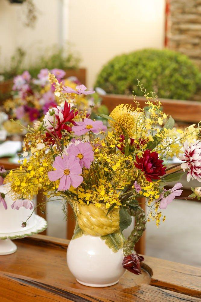 Amarelo, rosa, uva e vinho foram os tons dos arranjos feitos por Marcinho Leme, da Milplantas, em um lindo bowl e jarra com detalhes de banana. Usamos dálias, proteas high gold, orquídeas em tom de lilás e orquídeas chuva-de-ouro. Essa composição floriu tanto a nossa mesa principal, como o aparador que usamos para acomodar as comidas.