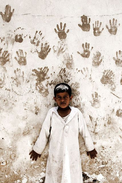 Boy in front of a wall with hand prints - Sanaa - Yemen by Eric Lafforgue on Flickr.Via Flickr: The hand print is supposed to bring luck. Many are found on the doors of the houses in Sanaa Yemen