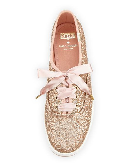 """kate spade new york glitter covered canvas sneaker. 0.8"""" flat heel. Round toe. Lace-up front. Logo patch stitched at tongue. Spade stud and Keds logo at back. Canvas lining and cushioned insole. Rubbe"""