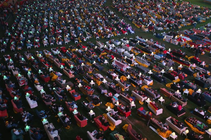 Fans reclining on sofas watch the Germany-Ghana World Cup match at a public viewing at the Alte Foersterei FC Union stadium on June 21, 2014 in Berlin, Germany. The stadium has allowed fans to bring 800 sofas that they've set up on the lawn to watch the World Cup matches on a giant monitor. (Photo by Sean Gallup/Bongarts/Getty Images)