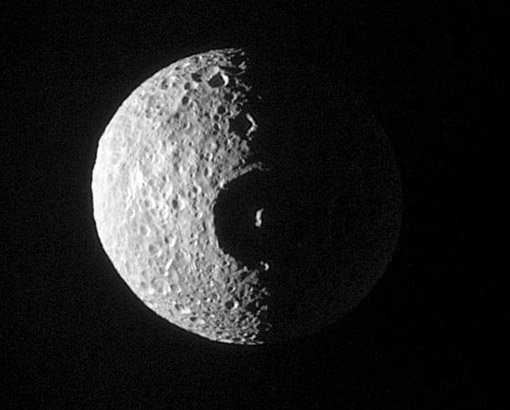 """Moons of Saturn : Mimas Discovery News Nope, this isnt the Death Star hanging around Saturn for its chance to blast Earth. This is Mimas, and it's a lucky survivor from an ancient, colossal collision. At 80 miles wide, the """"eye"""" -- called Herschel crater -- covers a good portion of the 247-mile-wide moon.  CREDIT: NASA/JPL/SPACE SCIENCE INSTITUTE."""