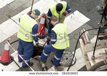 utility service company workers moves the manhole cover to cleaning the sewer line for clogs - stock photo