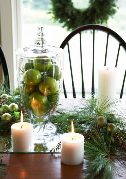 Green apples are the perfect hue for an easy Christmas display. Fill a glass jar with apples; mix in loose greens for a wintry feel. Place container on a beveled edge mirror (that serves as a table runner). Fill in with additional greens, ball ornaments and candles of different sizes.