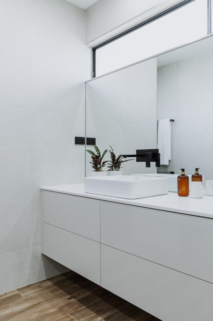 The White Bathroom Vanity And Wood Flooring And Set Off This