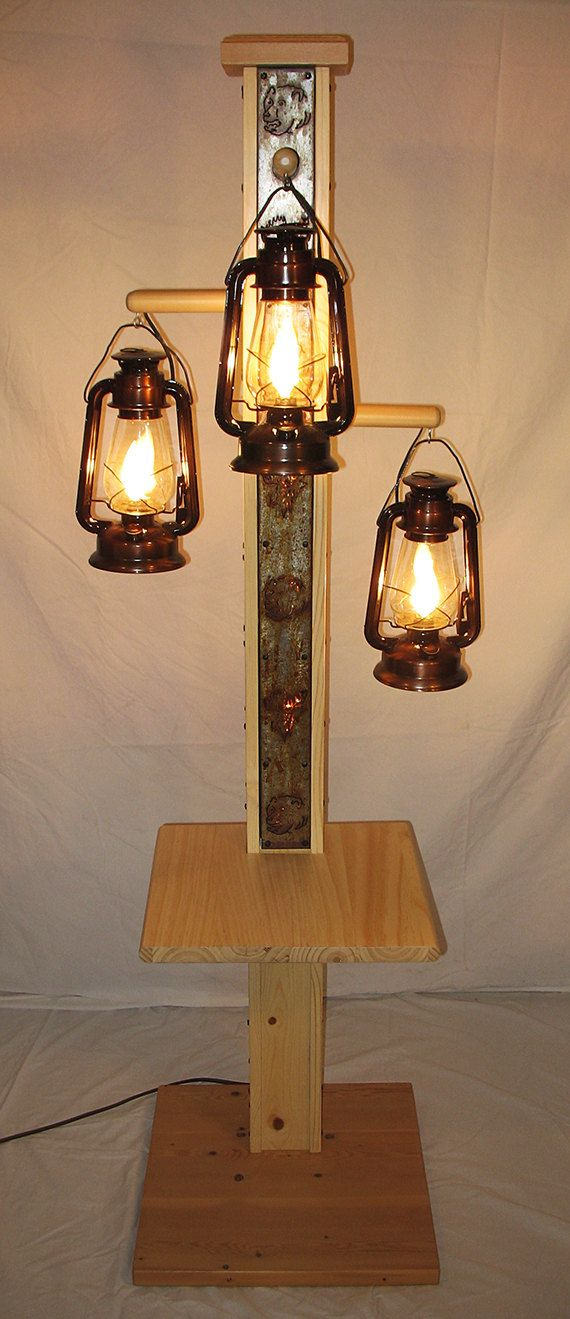 Rustic floor lamp with old fashioned electrified kerosene lamps. The center pole has bear and moose cutouts which emit light. One of a kind!