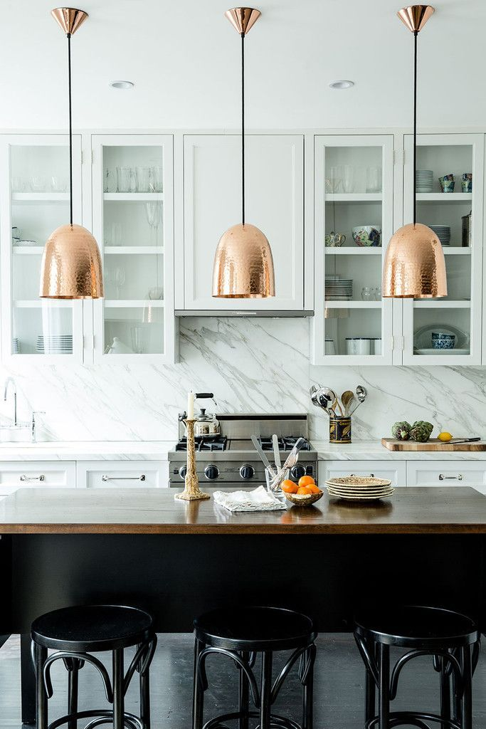 A Brownstone kitchen white with white cabinets marble black island. Brass pendants.