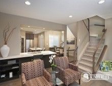 Great room, main staircase, open concept main floor. You can see the kitchen and open-to-above dining nook in the background. Luxury 3 bedroom townhomes. The Intrigue model, by Kimberley Communities.