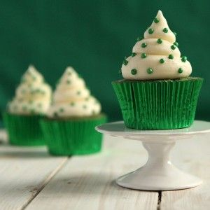 Three cupcakes in bright green paper cases topped with buttercream and green sprinkles