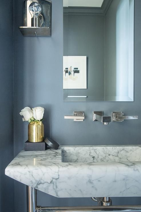 Gold and blue powder room boasts slate blue paint on walls lined with a frameless mirror over a wall mount faucet and a marble washstand.