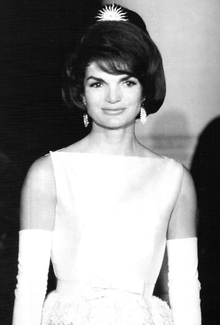 First Lady Jackie Kennedy at the White House state dinner, April 11, 1962, for the Shah of Iran and his empress. She is wearing a large sunburst pin of diamonds in her hair.