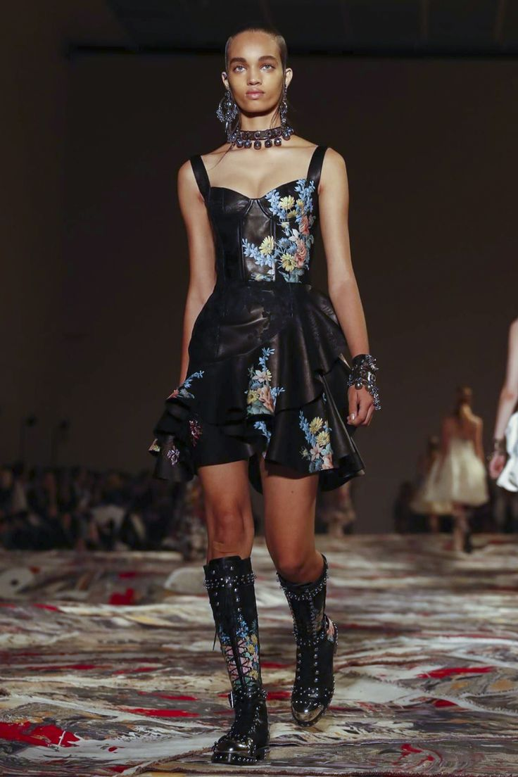 An imaginary island as a catwalk. A carpet strewn wilderness, encircling guests with rocks and gravel which wards off the celtic warriors imagined by Sarah Burton for Alexander McQueen. Wearing ins...