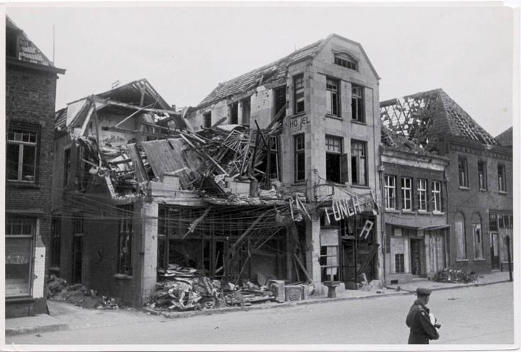 Een Britse militair staat bij het zwaar beschadigde hotel De Kroon aan de Markt.