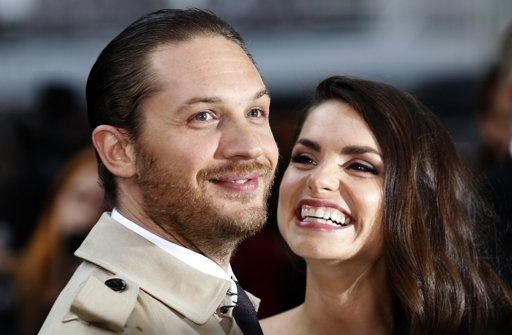 """British actor Tom Hardy and his girlfriend Charlotte Riley pose for photographers as they arrive at the European Premiere of """"The Dark Knight Rises"""" in Leicester Square, central London,"""