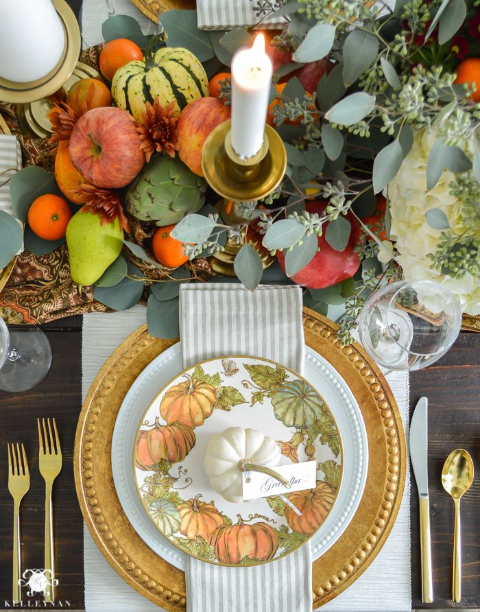 Thanksgiving Dinner Table Ideas - Gold Pottery Barn table setting with fruits, veggies, flowers, and eucalyptus