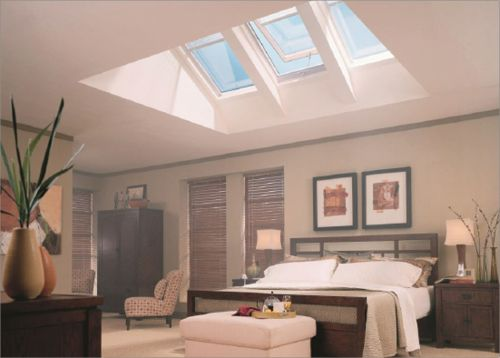 A bedroom is well lit by glazed windows in the roof that allow a lot of natural light in during the day.