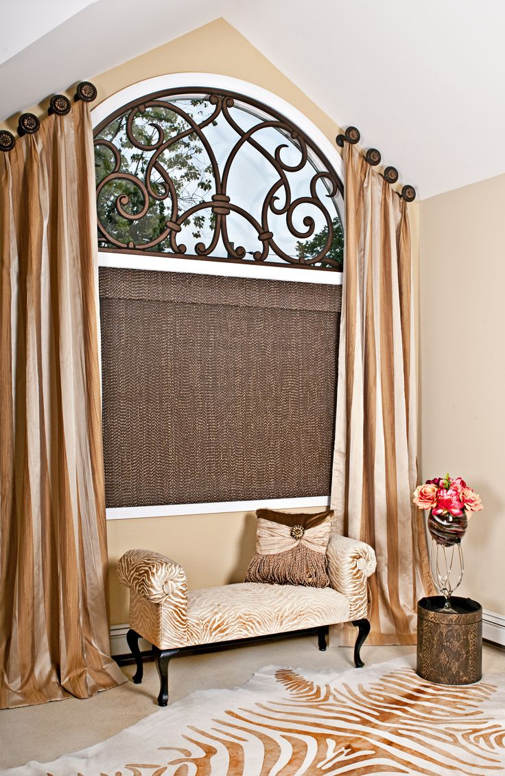 An arched window dressed in a beautiful angled panels, finished with a custom faux iron piece and a woven woods with silk window shade, gives this room a very romantic and luxurious look. Designed by Yelena Gerts Decorating Den Interiors NYC.
