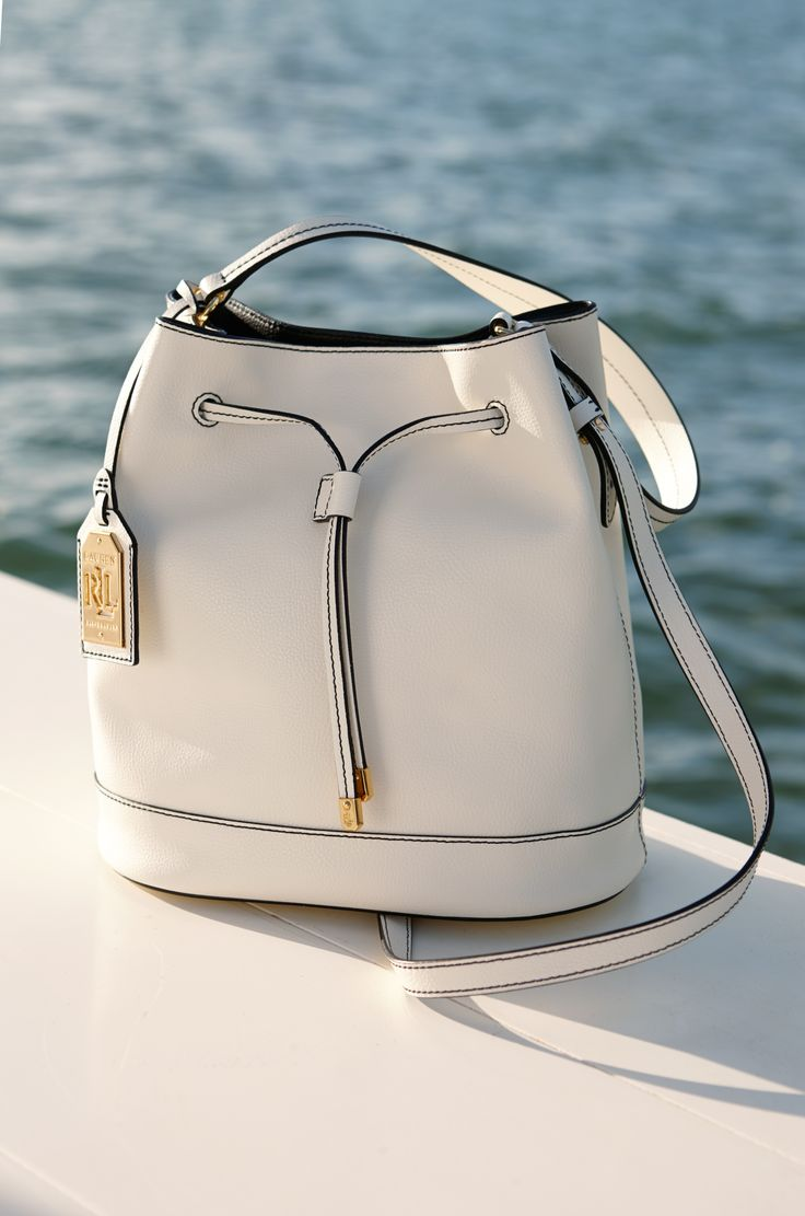 """Lauren Ralph Lauren White Leather Drawstring Bag: With a sleek silhouette, the Crawley Leather Drawstring Bag is a wear-anywhere style that is accented with our gold-toned signature """"LRL"""" monogram. Carry yours by its top handles or shoulder strap."""