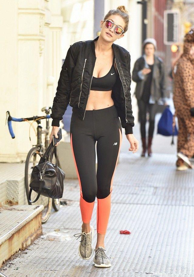 Gigi Hadid wears a Nike sports bra, black and orange leggings, a bomber jacket, Yeezy Boost sneakers, and mirrored Dior sunglasses