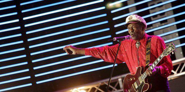 Chuck Berry im roten Hemd mit Kapitänsmütze und einer Guitarre im Arm