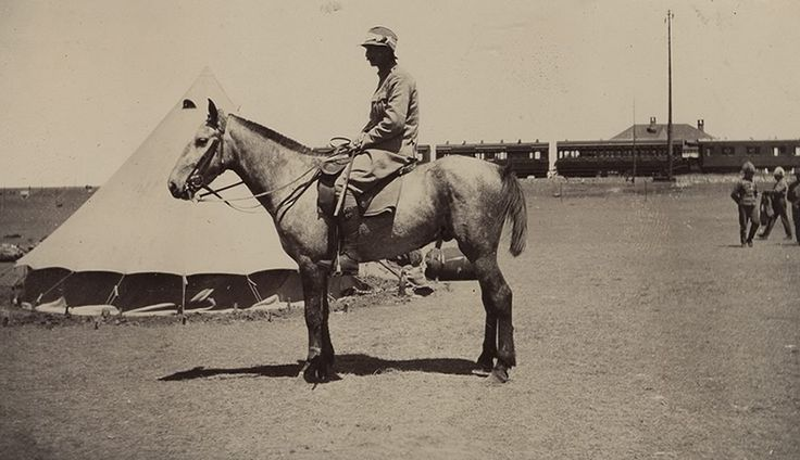 Mounted soldier of The Cameronians (Scottish Rifles) at camp in South Africa, with Greylingstad Train Station in the background.