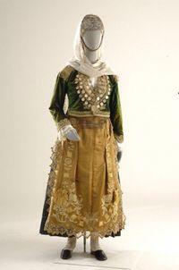 Γυναικεί φορεσιά από τα Μέγαρα Description: Στην τοπική ορολογία η μεγαρίτικη νυφική φορεσιά ονομάζεται κατηφένια. Βασικό εξάρτημά της είναι το φουστάνι αναγεννησιακού τύπου, που το χρώμα του υποδηλώνει την ηλικία της γυναίκας (πράσινο γιατις νέες, μπλε για τις ηλικιωμένες). Πάνω από αυτό φορούν το βελούδινο ζιπούνι με τα χρυσοκεντήματα ενώ η ποδιά είναι επηρεασμένη από σχέδια περιοδικών μόδας της εποχής. Το στήθος καλύπτεται με άλυσες ή καδένα ενώ το κεφάλι στολίζεται από το φέσι με τους…