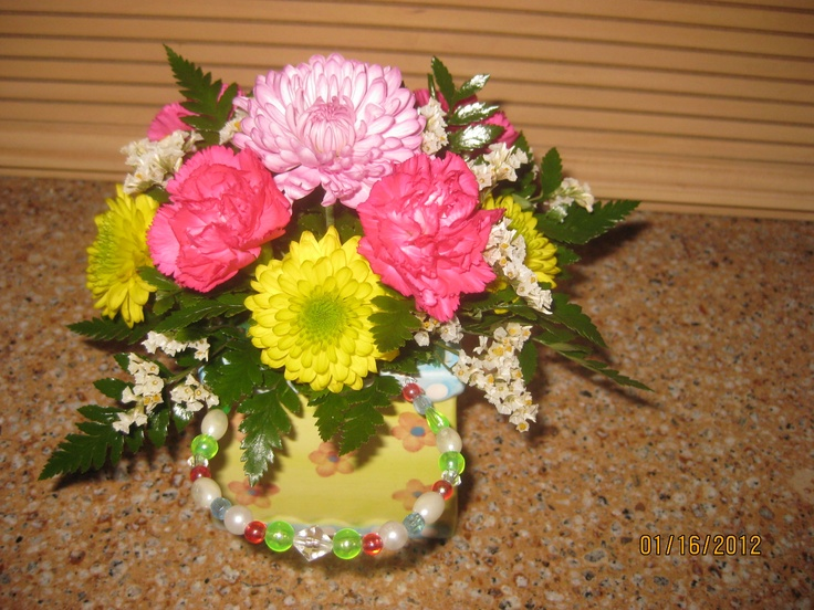 Bright flowers arranged in a thrftt store ceramic purse with beaded handle.